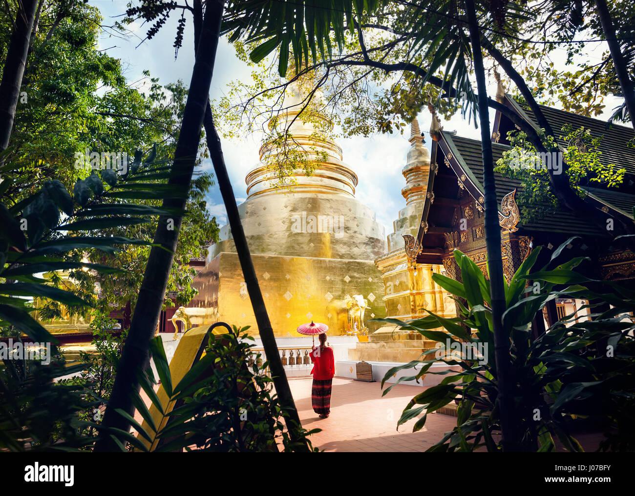 Tourisme Femme avec parapluie traditionnel Thaï rouge près de Golden temple Wat Phra Singh de Chiang Mai, Thaïlande Banque D'Images