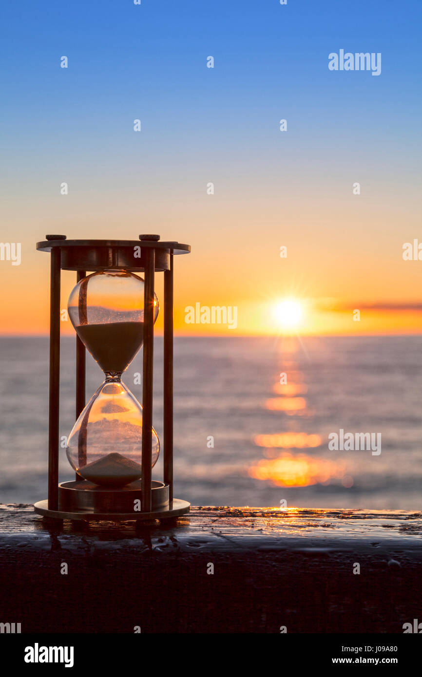 Sablier ou horloge de sable en face d'un merveilleux clair lever ou le coucher du soleil. Banque D'Images