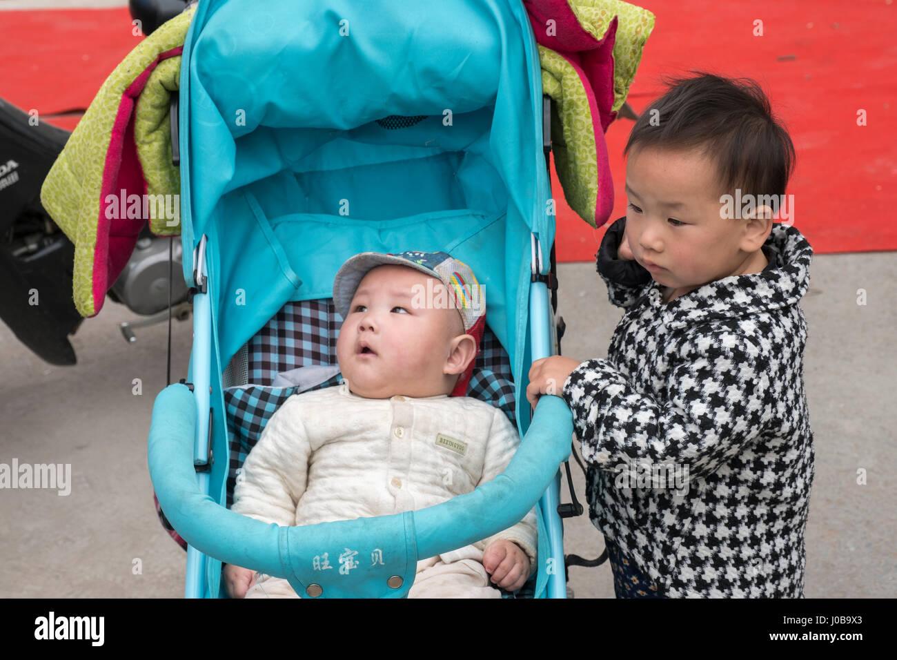 Une soeur et son frère nouveau né dans le comté de Xiong, Baoding, Chine. La nouvelle politique de Photo Stock