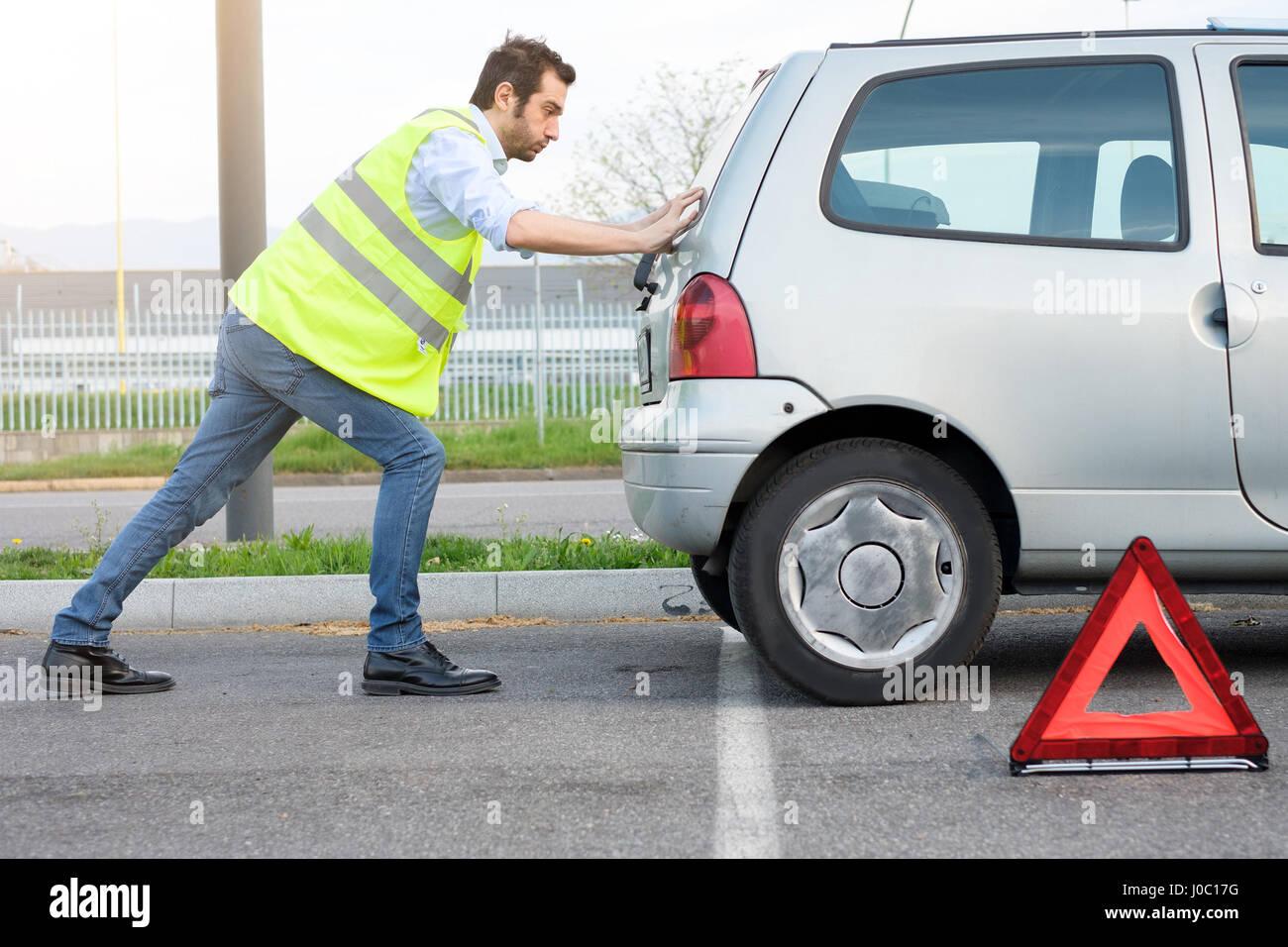 A souligné l'homme en poussant sa voiture après panne de moteur Photo Stock