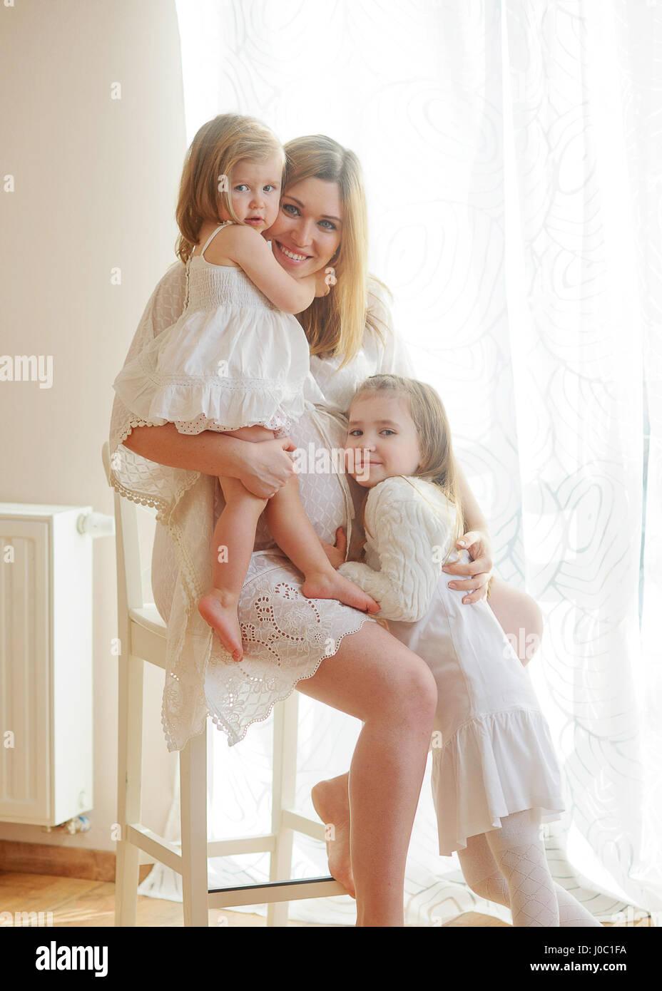 belle femme enceinte avec deux filles femme en robe blanche est assis sur une chaise elle. Black Bedroom Furniture Sets. Home Design Ideas