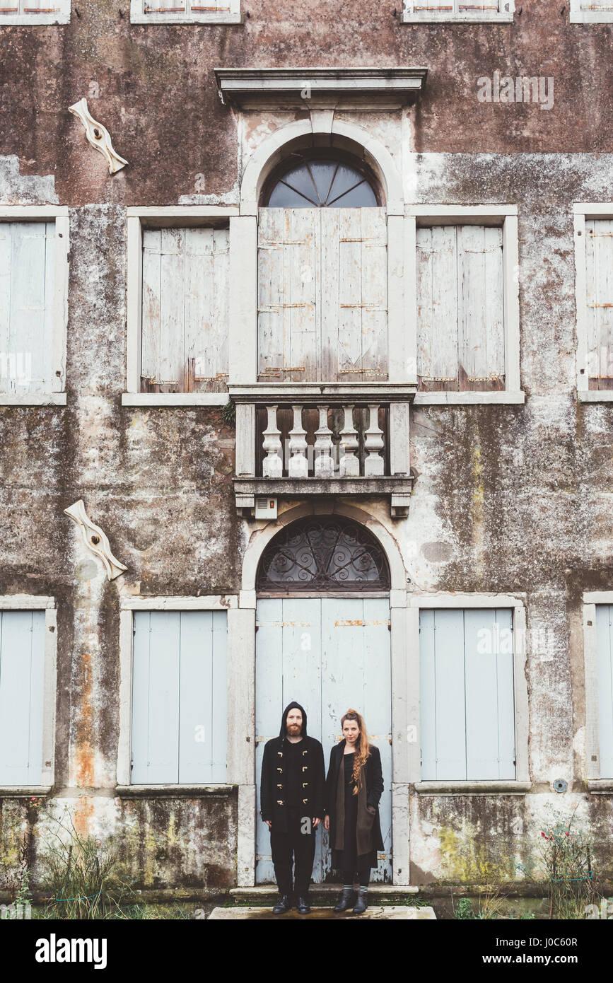 Portrait of couple debout à la porte de l'ancienne maison Photo Stock