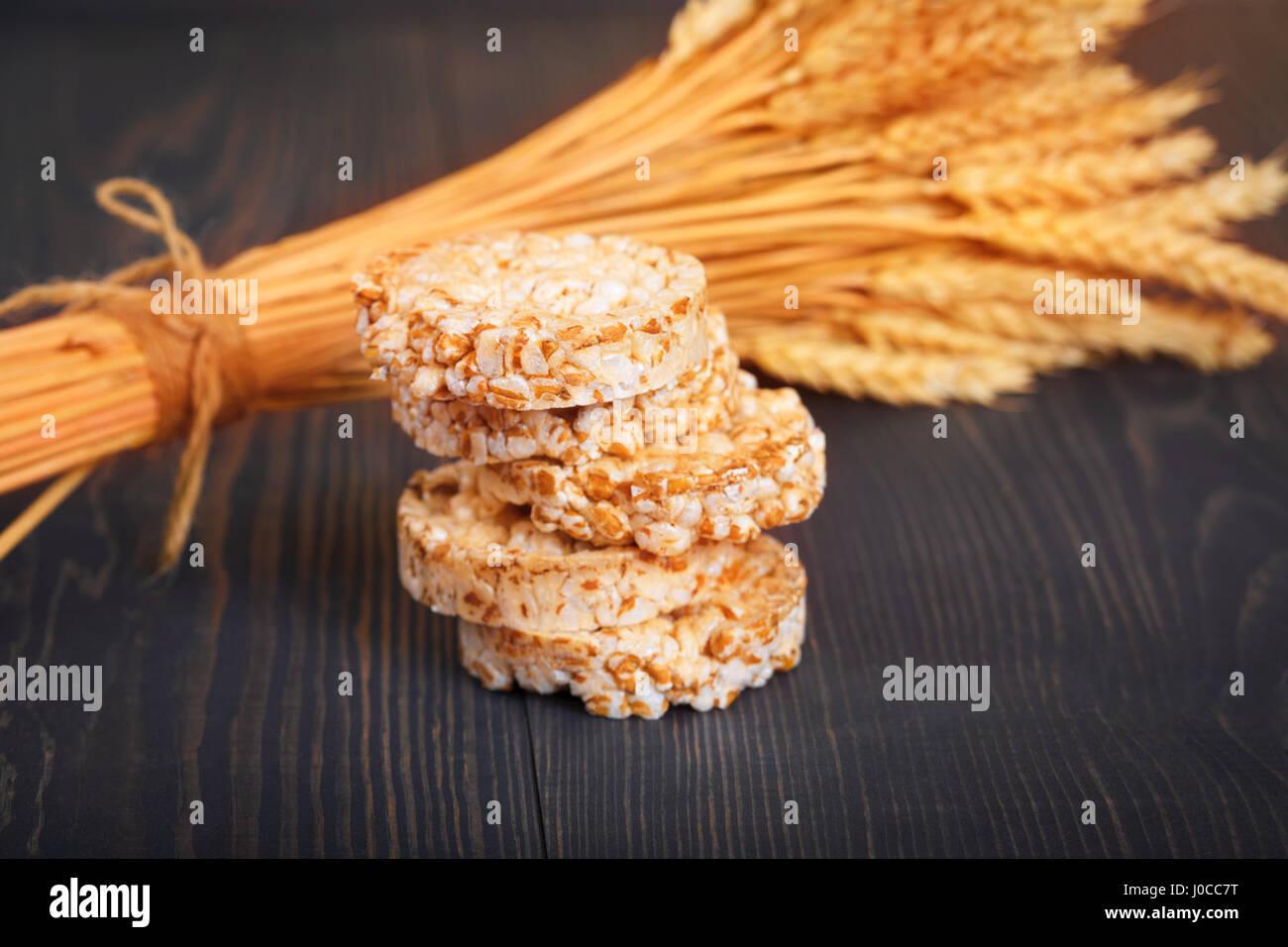 Un régime alimentaire faible apport calorique sur craquelins de grains un fond en bois sombre. Photo Stock