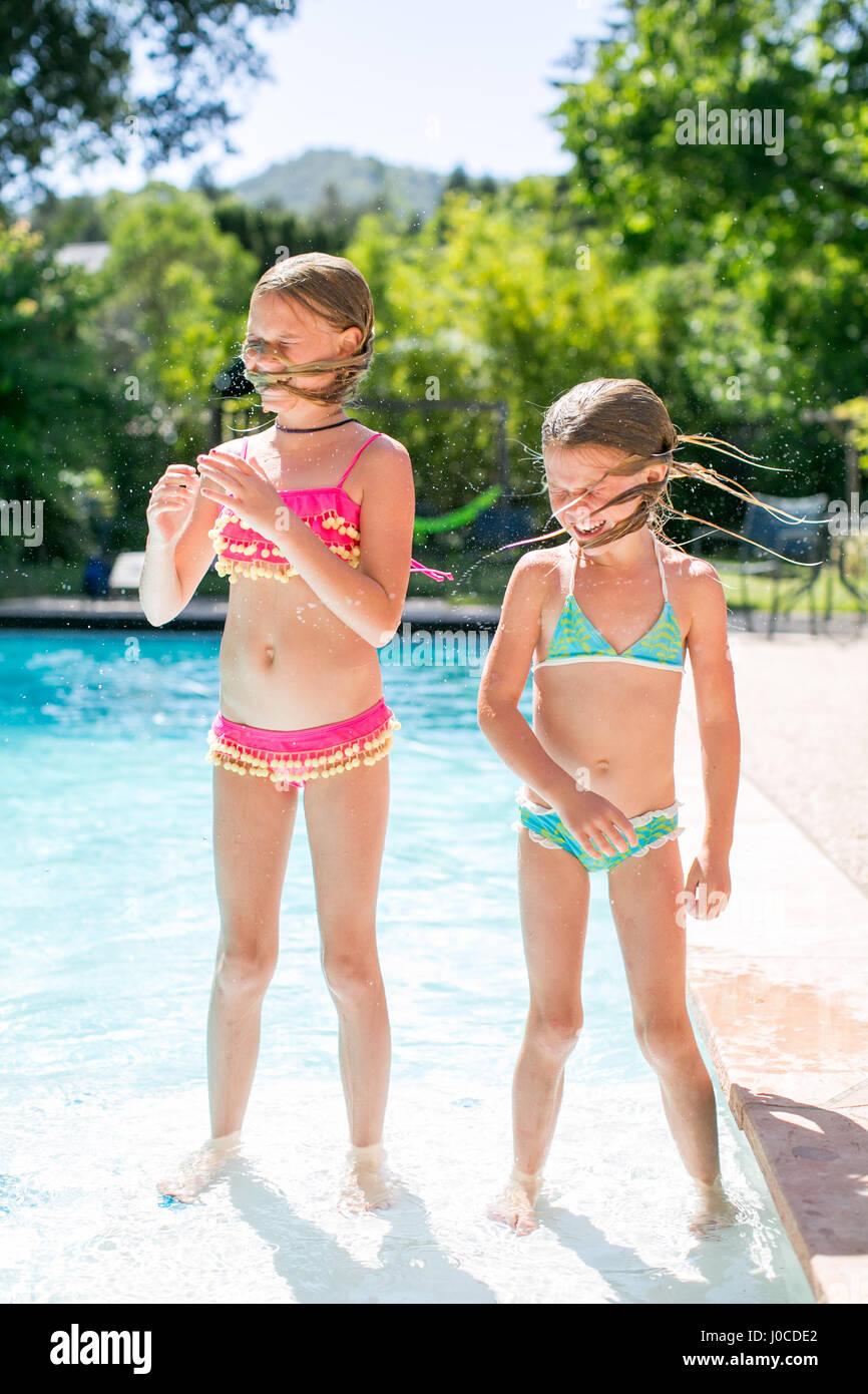 Deux sœurs secouant les cheveux mouillés par piscine extérieure Photo Stock