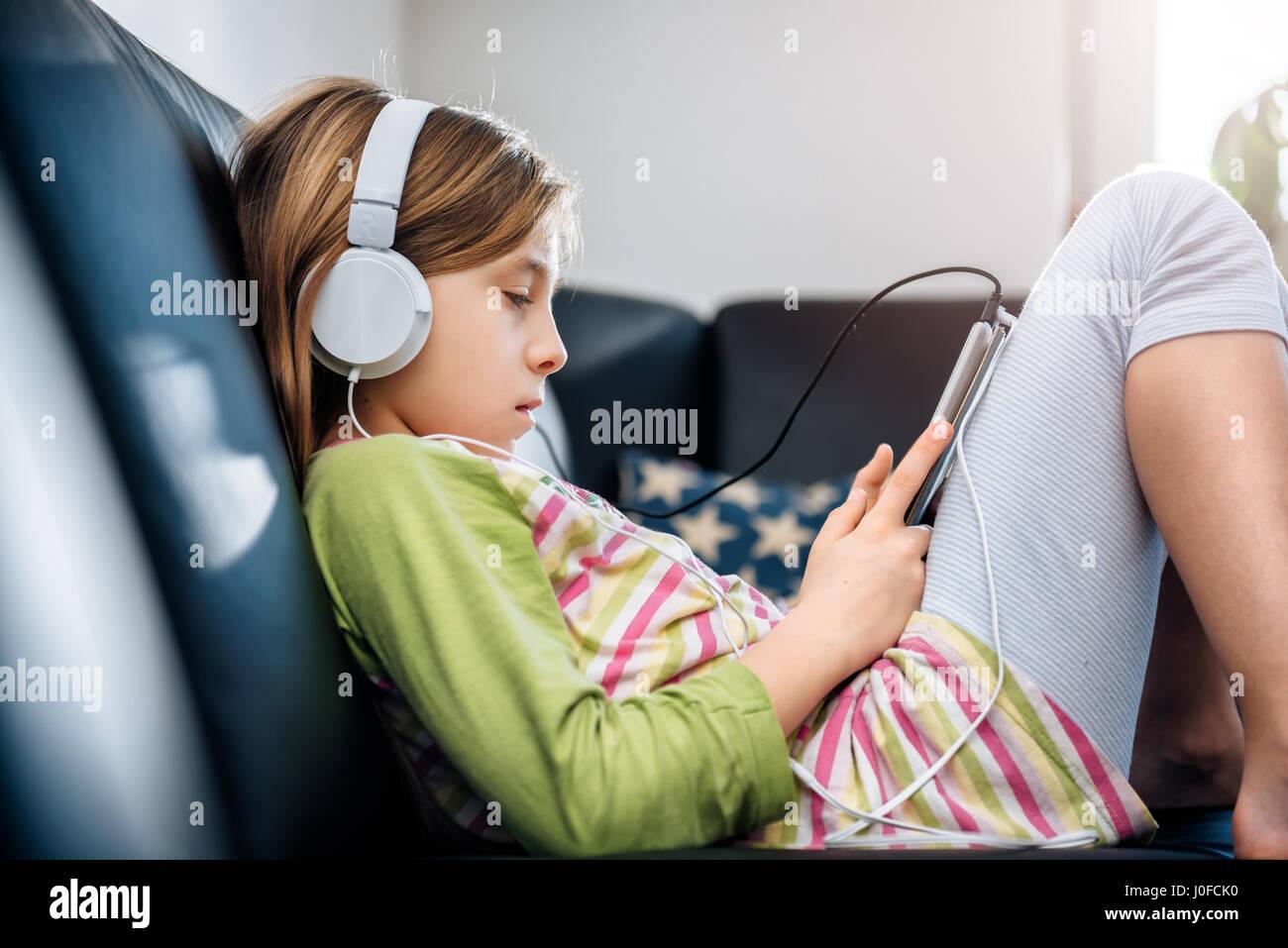 Black girl sitting on sofa using tablet et listening music Banque D'Images