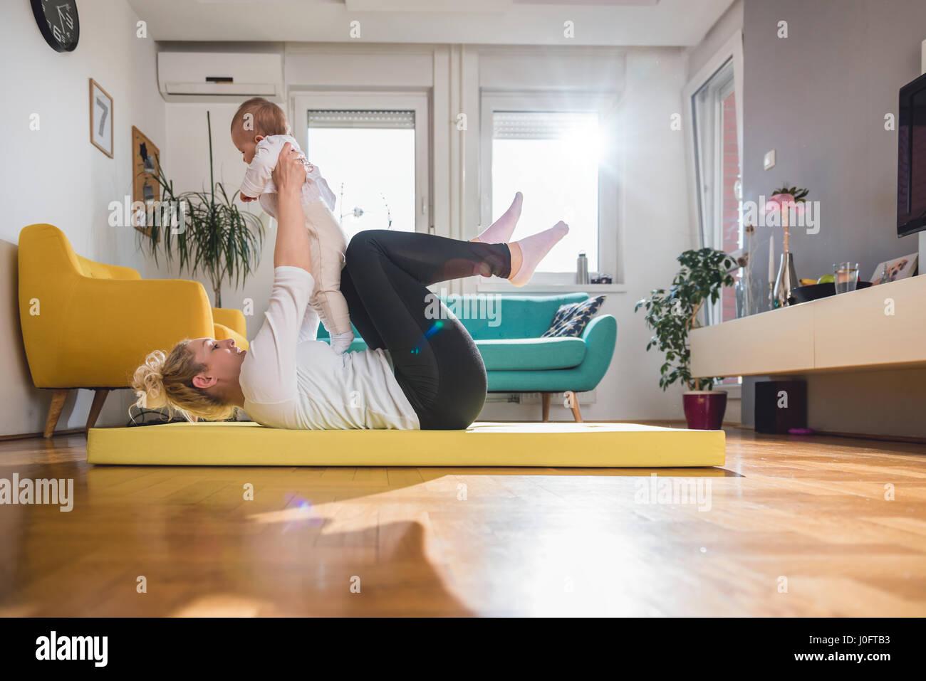 L'exercice de la mère avec son bébé sur le tapis à la maison jaune Banque D'Images