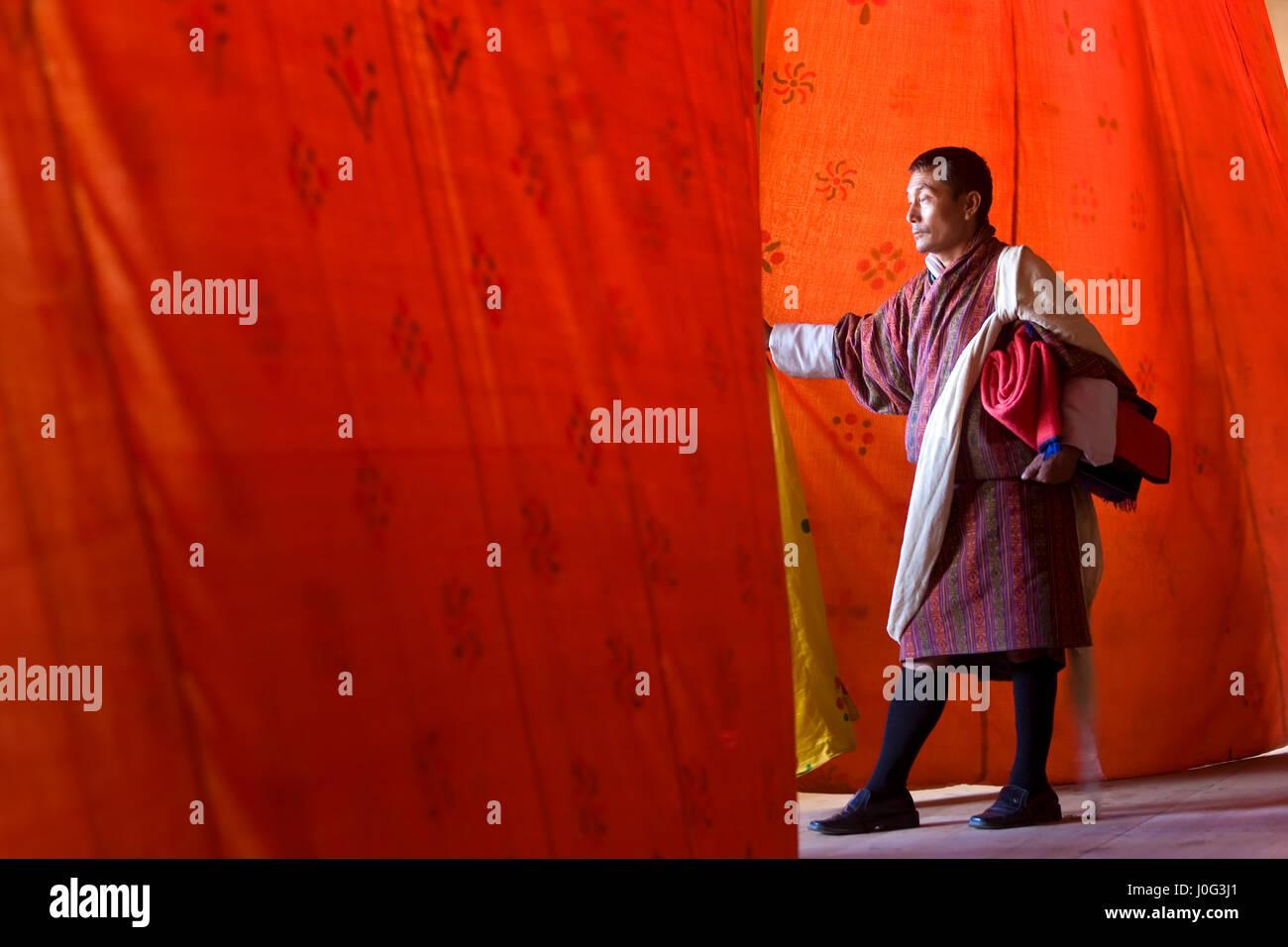 L'homme regardant à travers les rideaux à la performance, Festival, Trashichhoe Dzong, monastère, Photo Stock