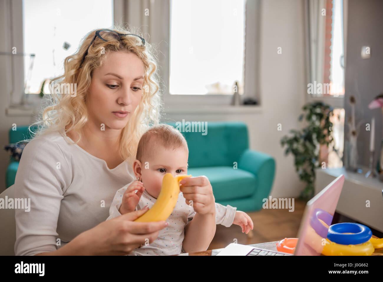 Peler les bananes de la mère de son bébé au bureau à domicile Photo Stock