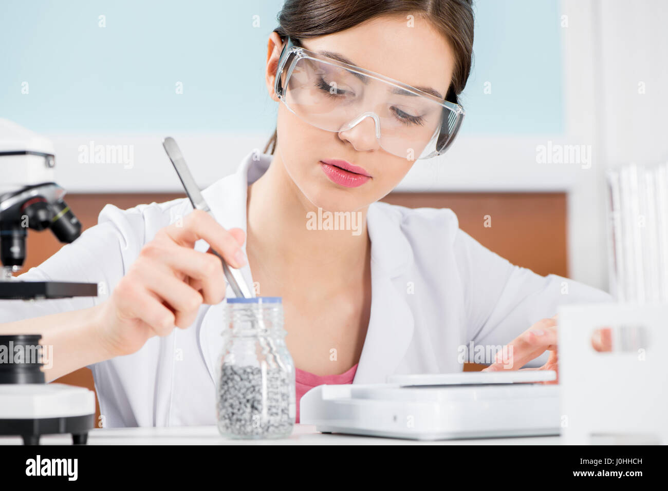 Young female scientist in lunettes de protection travaillant avec le  réactif de laboratoire en Photo Stock d0a7ce04bd30