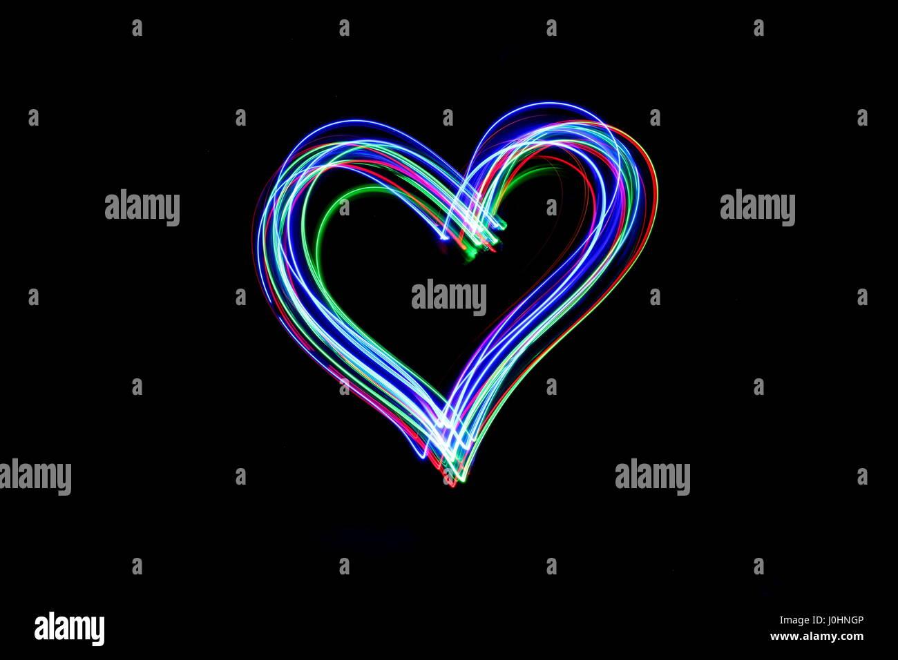 La lumière peinture photographie - longue exposition photo de fairy lights, en forme de coeur sur fond noir. Abstract Neon contours symbole. Banque D'Images