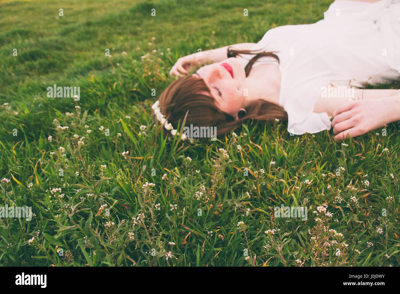 Jeune femme hippie sur un champ vert couchage Photo Stock