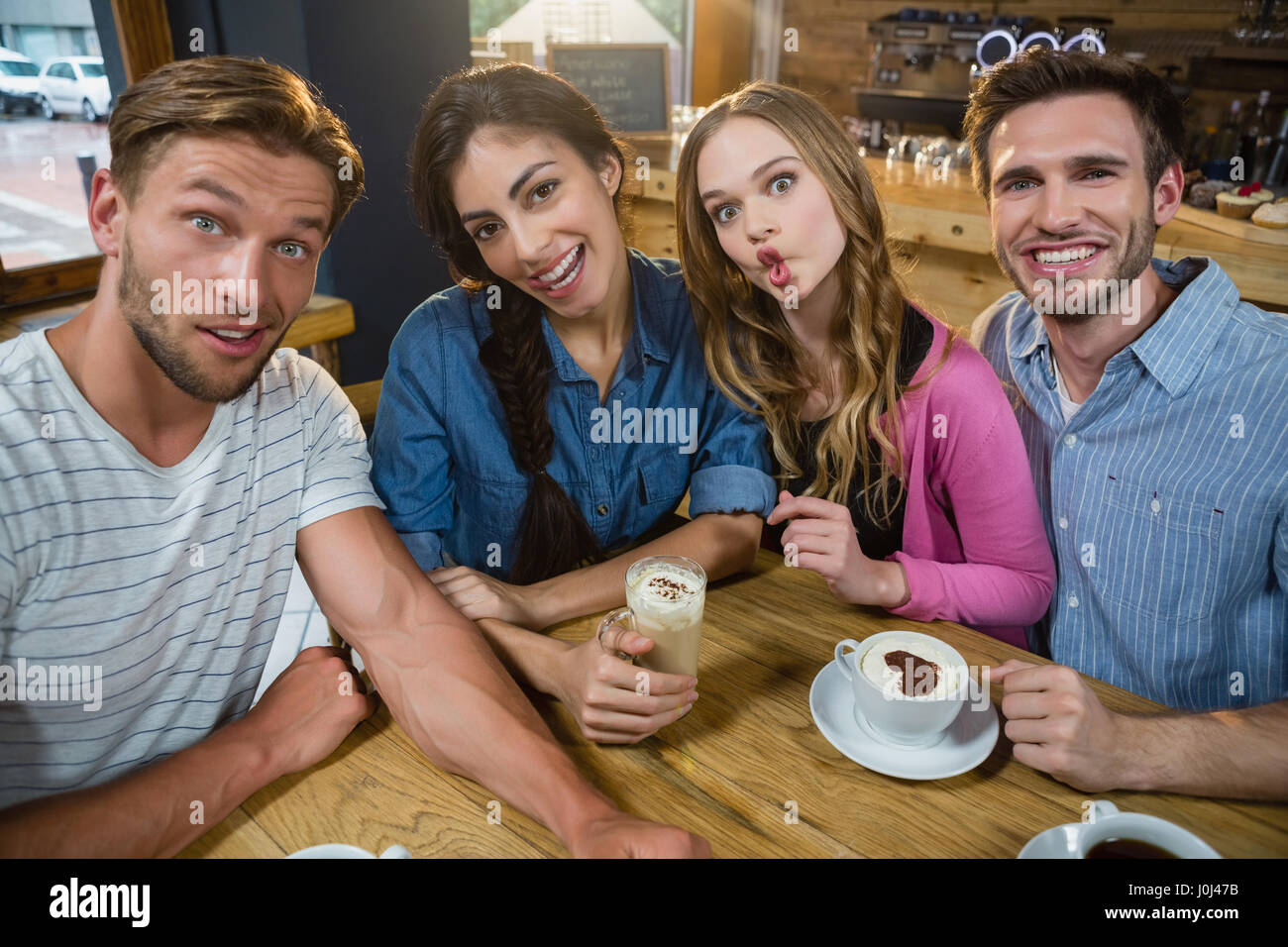 Portrait of happy friends making faces while having coffee in café Photo Stock