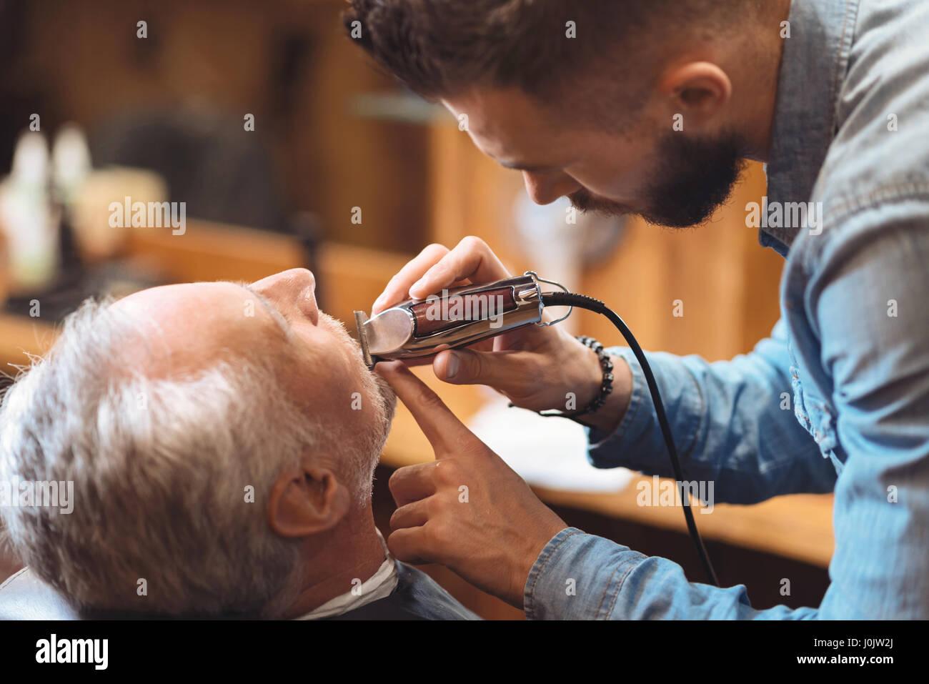 Coiffure charismatique barbe en forme du client dans le barbershop Photo Stock