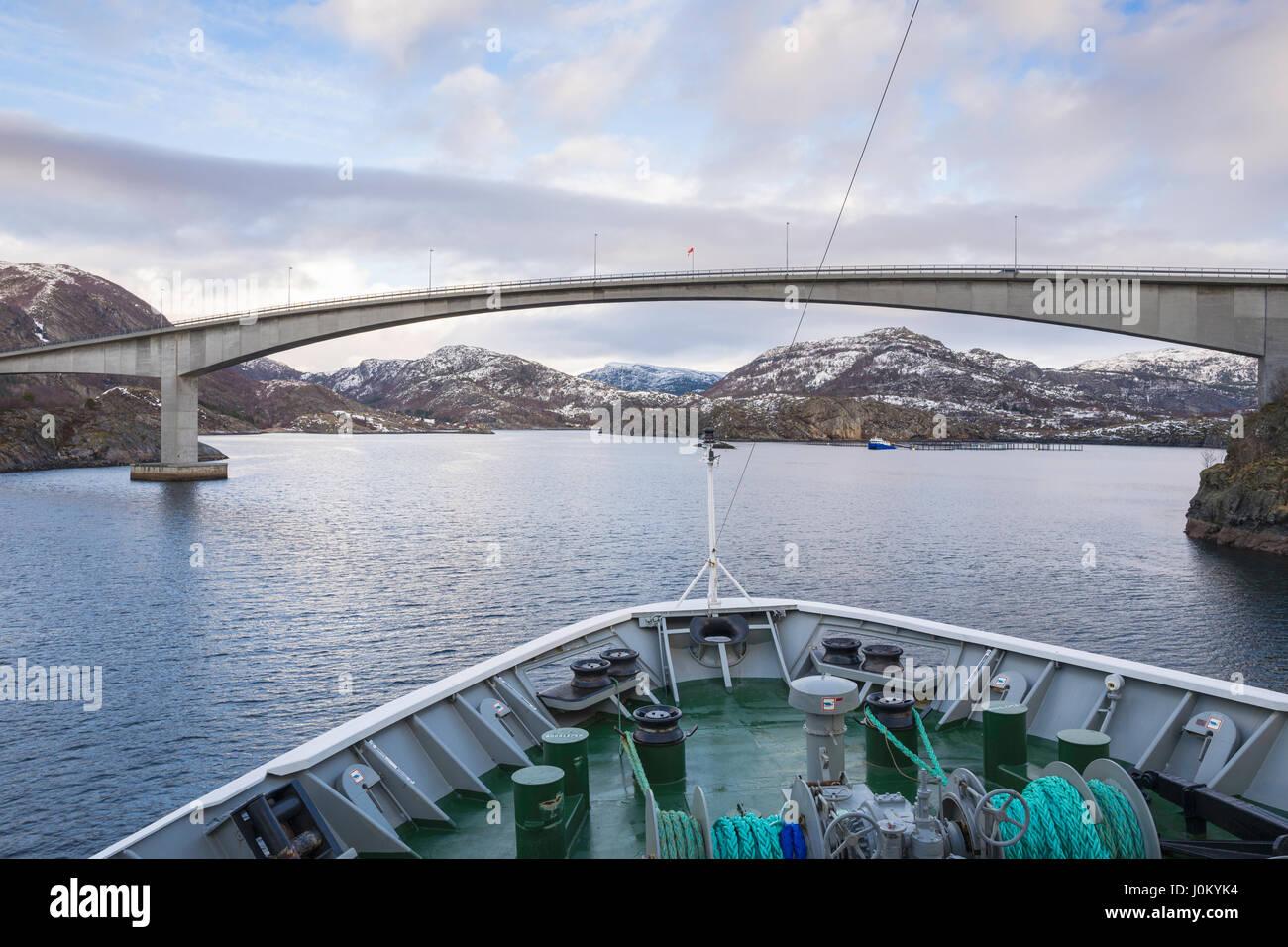 Navire Hurtigruten, Mme Richard avec, fait son chemin à travers l'étroit détroit de Stokksund, la Norvège, sous l'autoroute 723 Pont à Stokknes. Banque D'Images