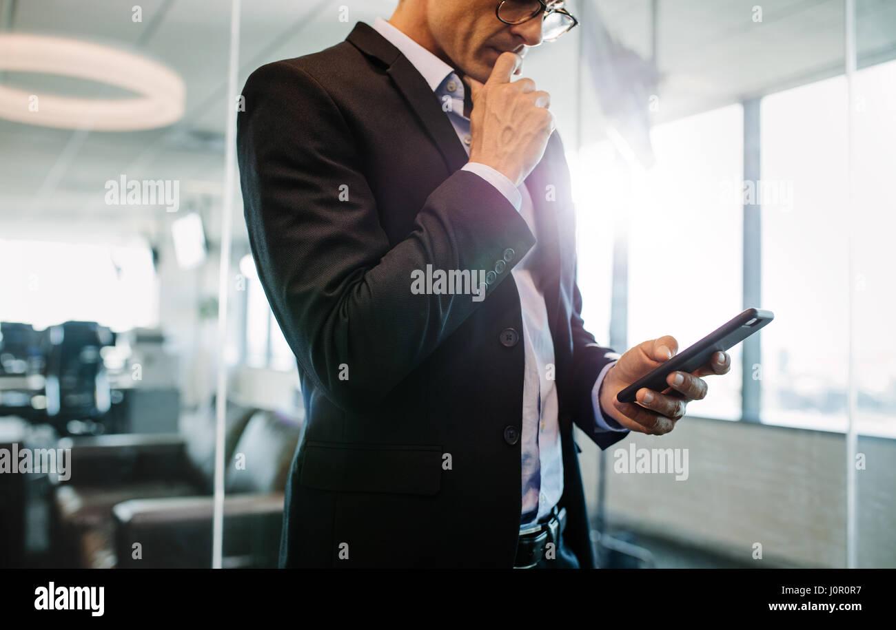 Cropped shot of woman in office et de penser. Male executive holding smart phone. Banque D'Images