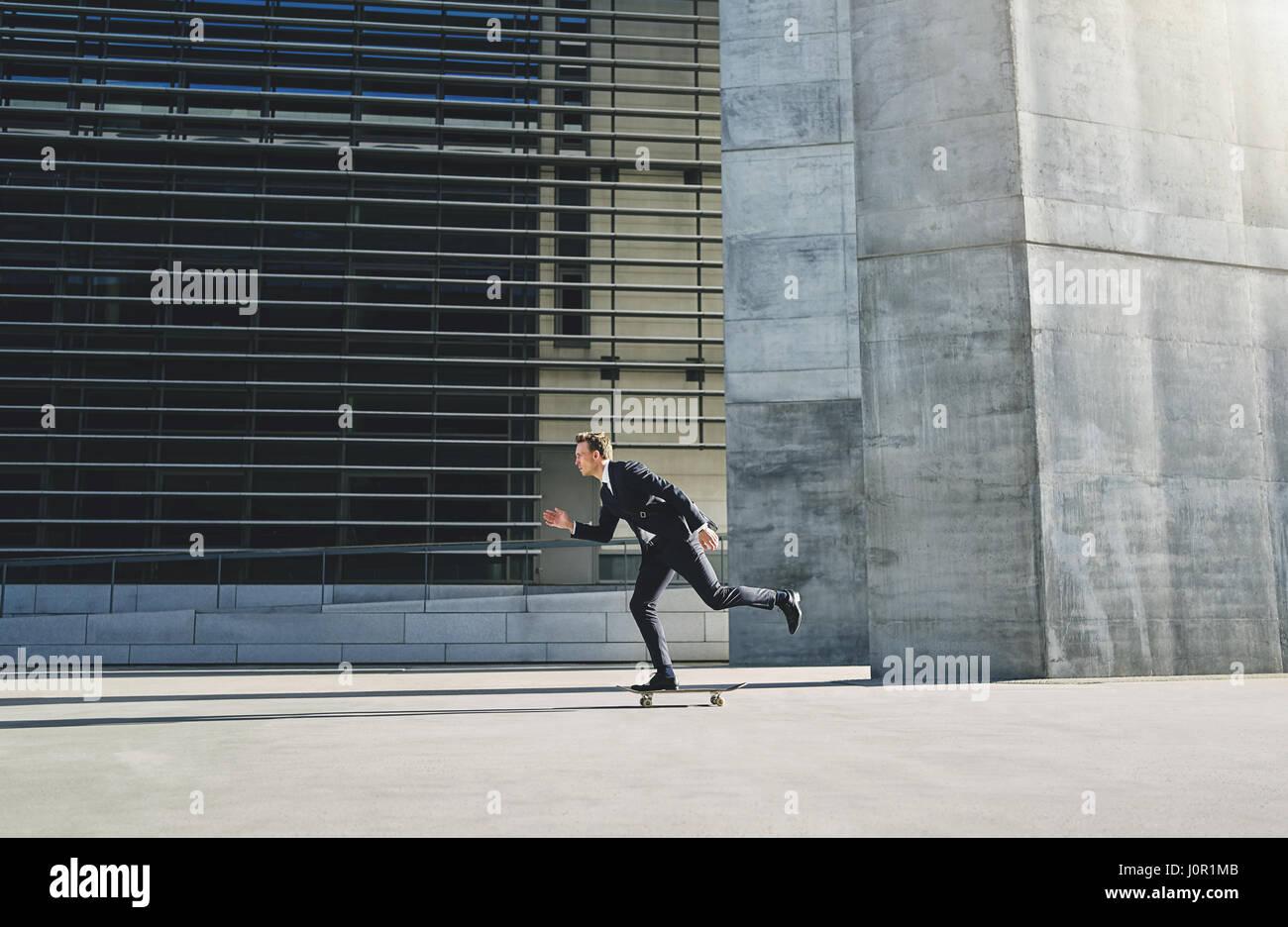 Dans un costume d'affaires déménagement, une grande vitesse d'une planche à roulettes Photo Stock