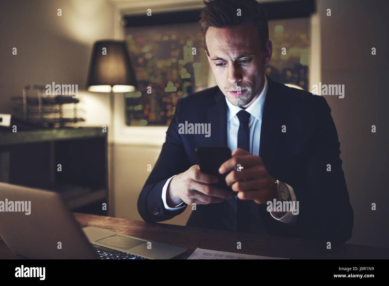 La personne intelligente en utilisant son smartphone sur le lieu de travail de nuit. Photo Stock