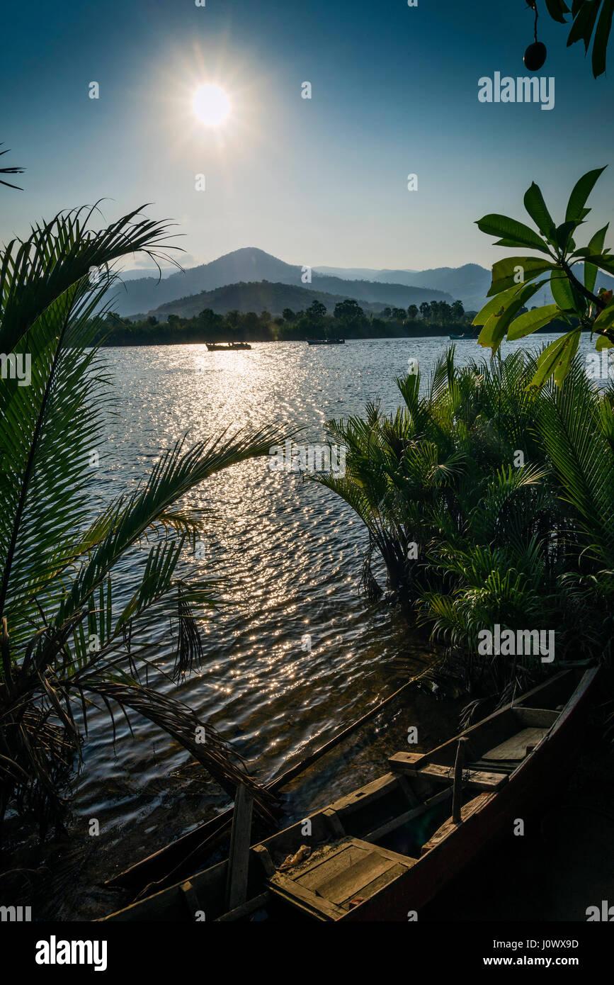 Le coucher du soleil exotique tropical sur Riverside à Kampot Cambodge Asie avec bateau de pêche Photo Stock