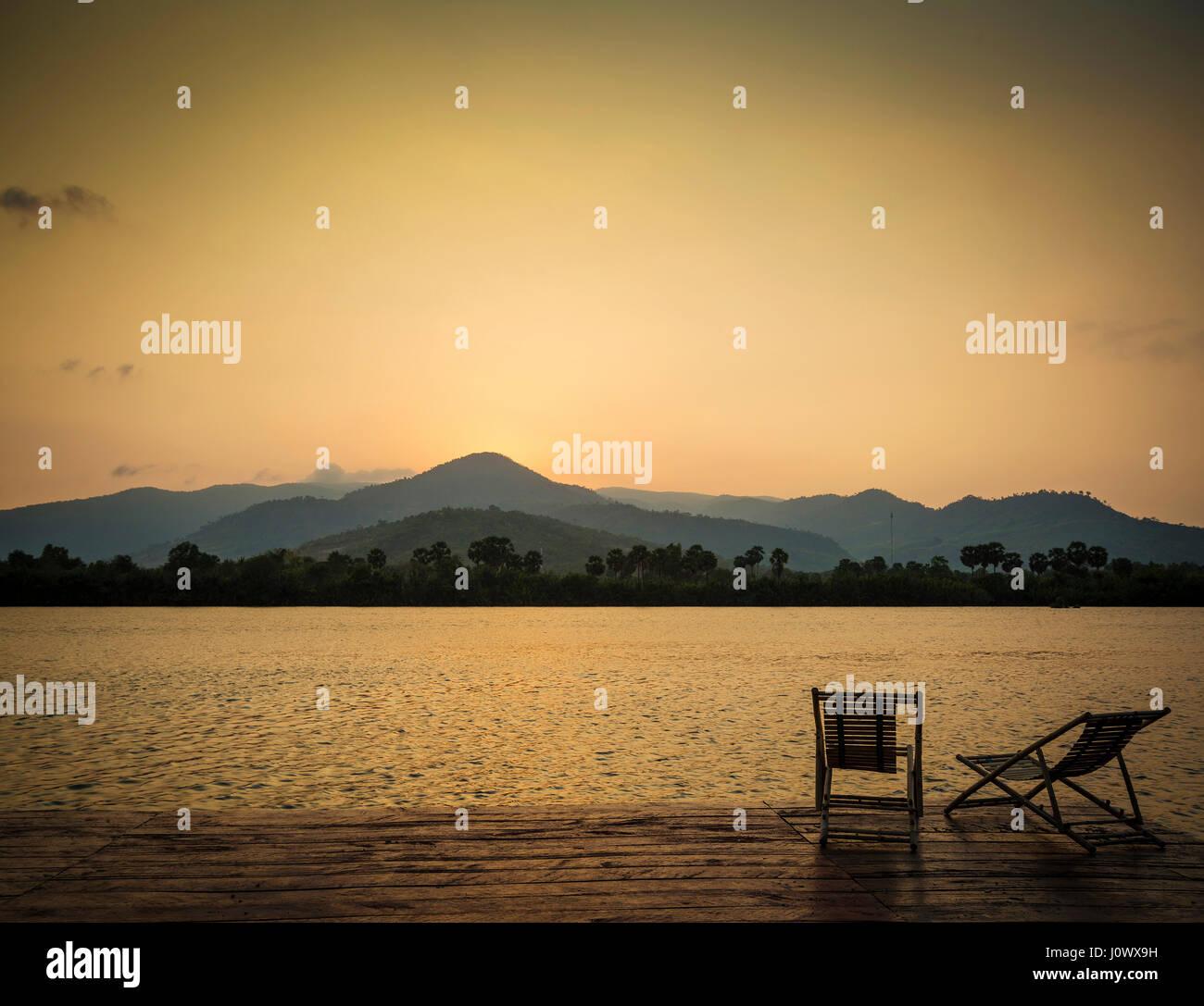 Le coucher du soleil exotique tropical sur Riverside à Kampot Cambodge Asie avec transats Photo Stock