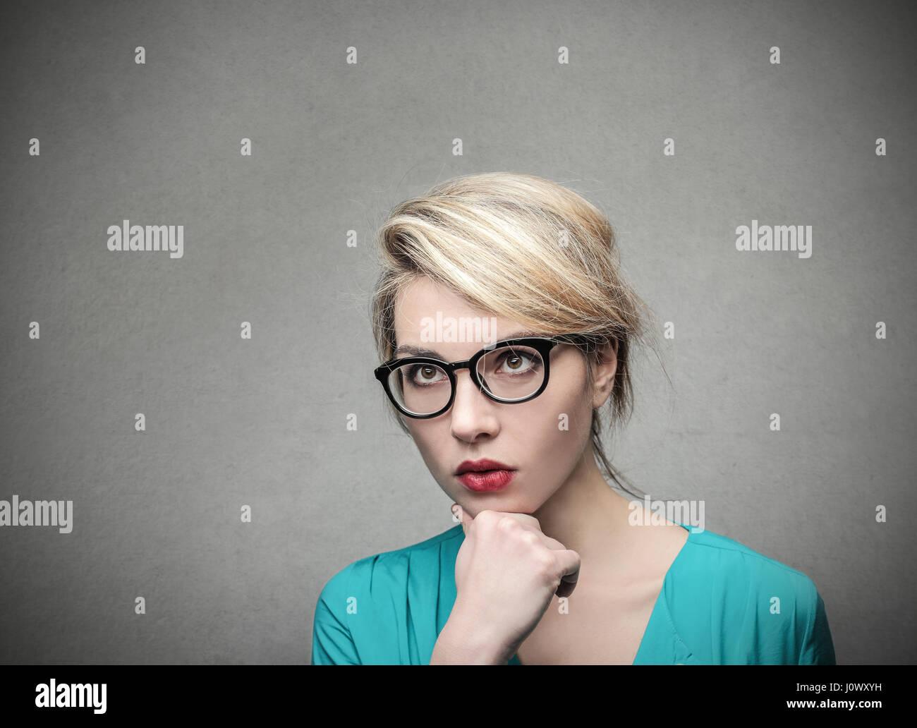 Femme blonde lunettes en pensant Photo Stock
