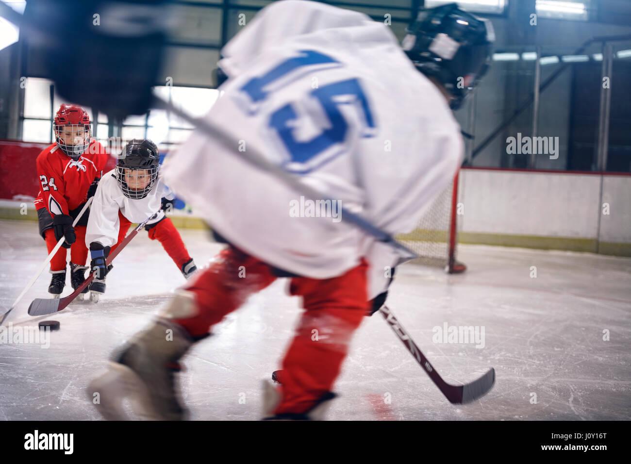 Petit Garçon jouant sur la patinoire de hockey sur glace Photo Stock