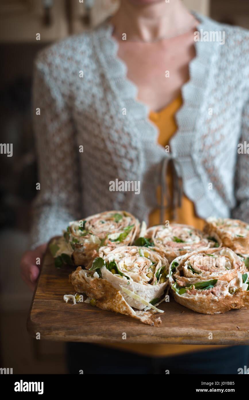 Roule avec du thon et des verts sur la planche de bois dans le Woman's hands Photo Stock