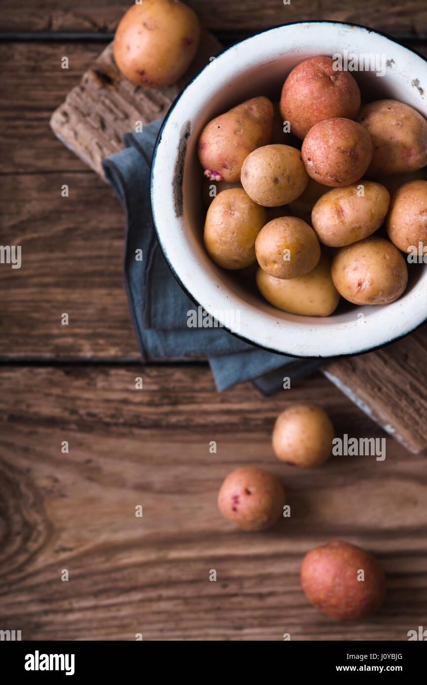 Les pommes de terre crues dans le bol en métal sur la table en bois Vue de dessus Photo Stock