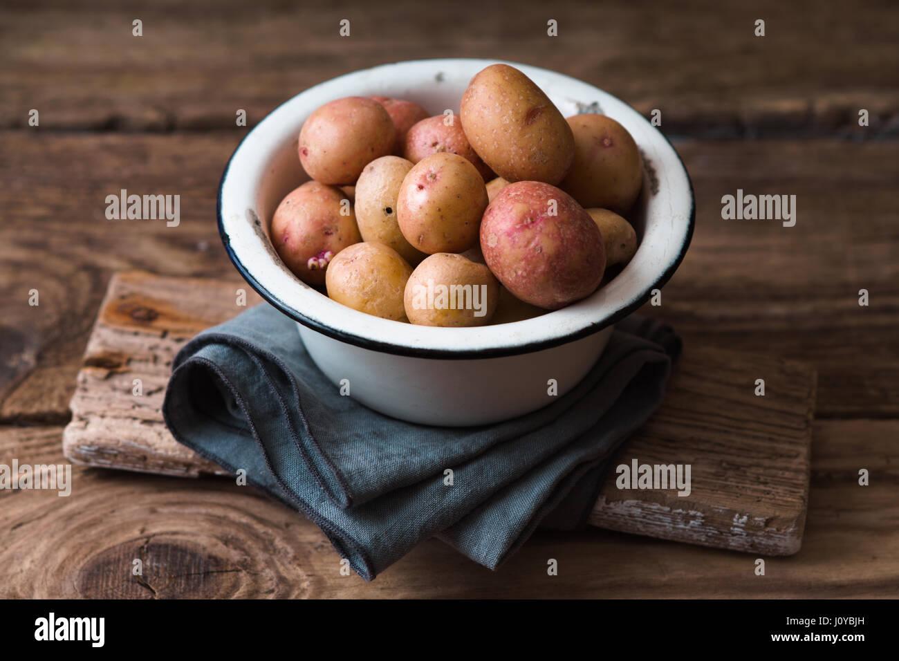 Les pommes de terre crues dans le bol en métal sur la table en bois Photo Stock