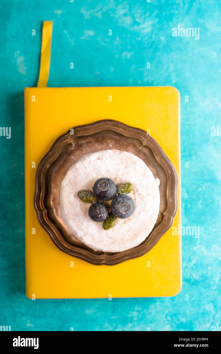 Gâteau avec blueberry sur un bloc-notes jaune espace libre Photo Stock