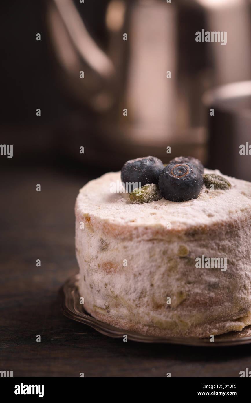 Cake aux myrtilles et pistaches contre une théière Photo Stock