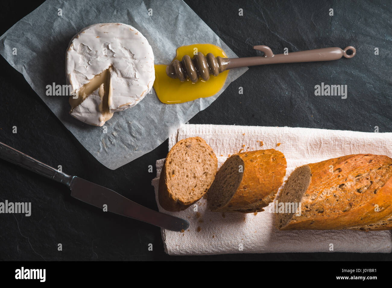 Fromage Brie, morceaux de pain baguette, du miel sur parchemin Photo Stock