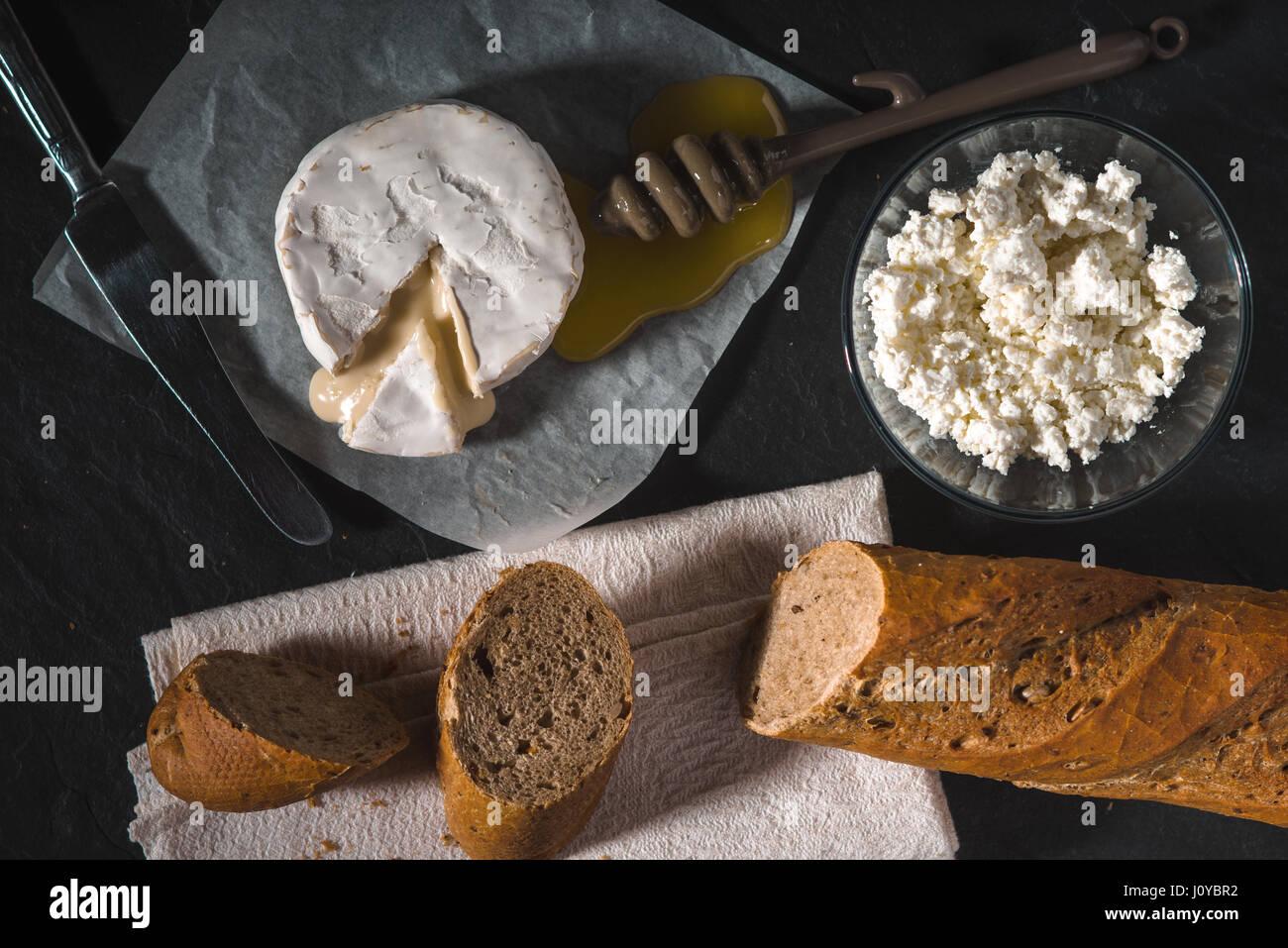 Fromage Brie, le fromage cottage, le miel sur parchemin Photo Stock