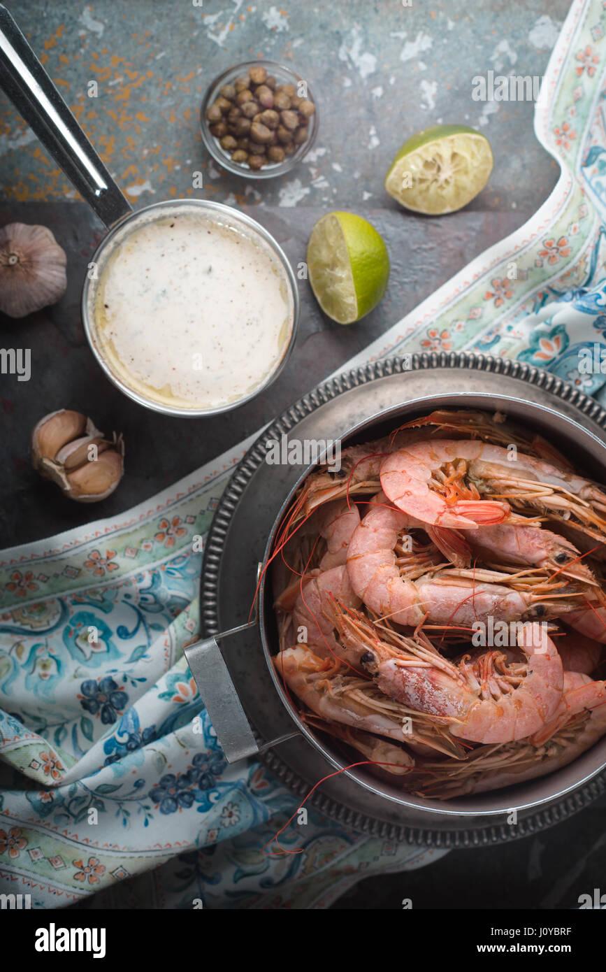 Crevettes dans un bol, la sauce, les câpres et l'ail sur ardoise Photo Stock