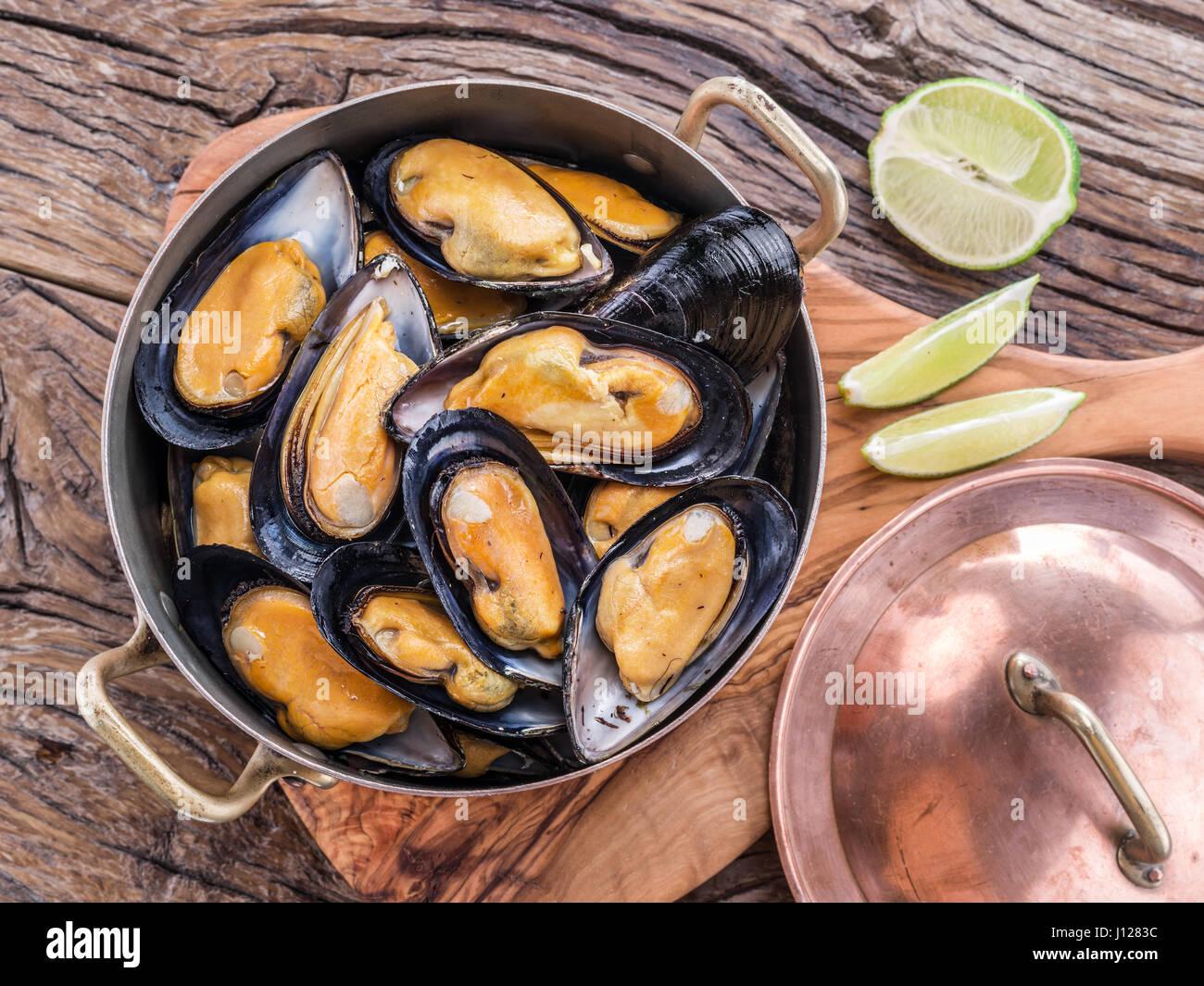 Les moules cuites en pan de cuivre sur la table en bois. Photo Stock