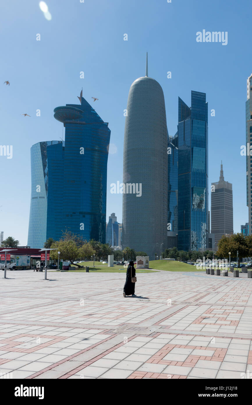 La ville de Doha, au Qatar, au Moyen-Orient, une femme marche loin de porter un appareil photo Shayla sur sa tête Photo Stock