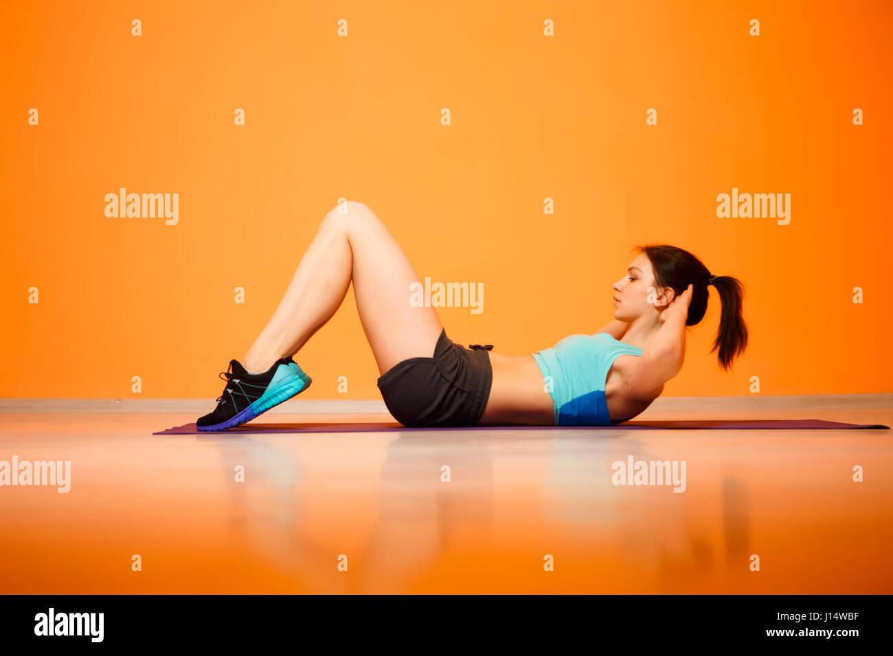 Brunette faisant des exercices sur un tapis Photo Stock