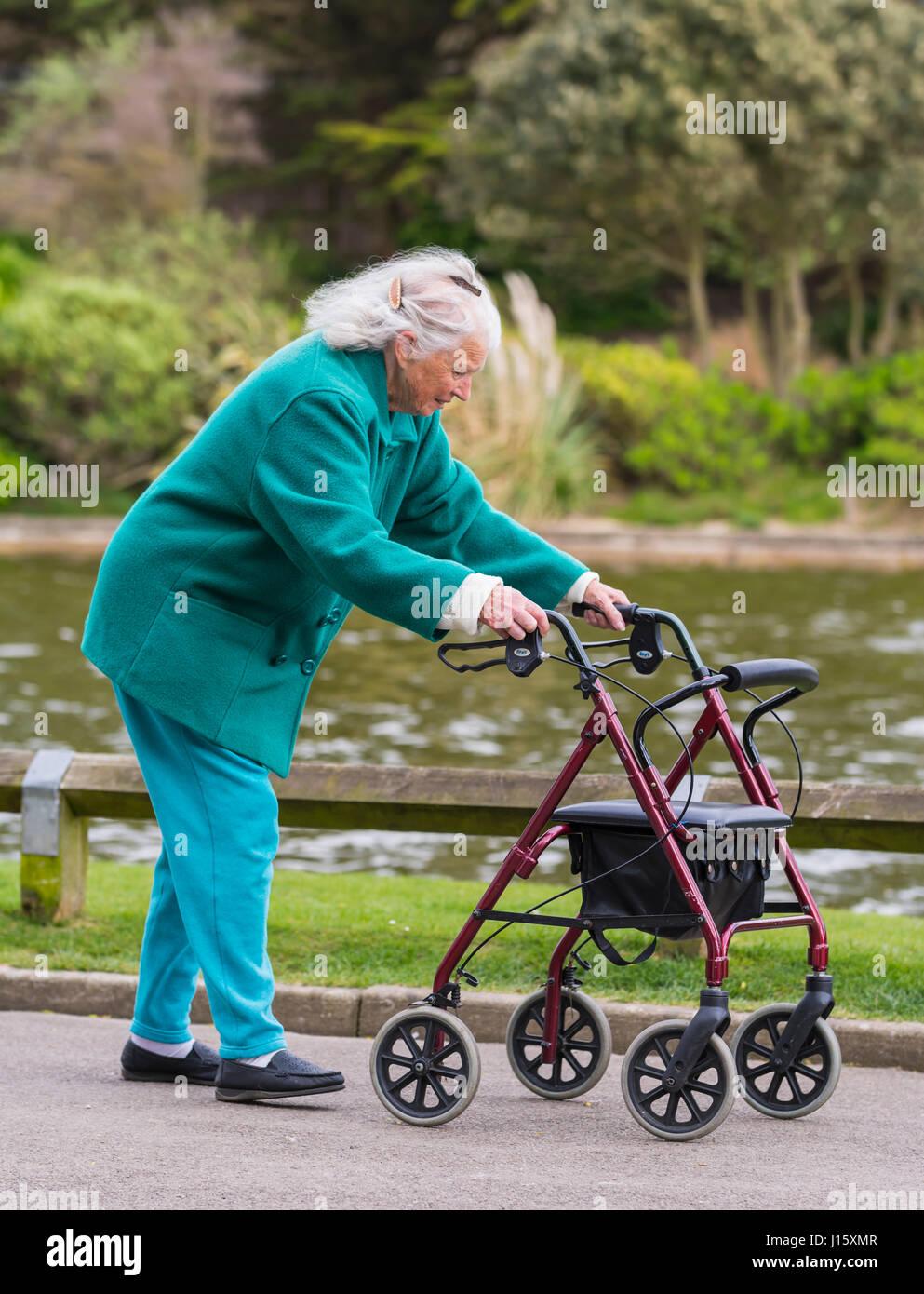 Dame âgée marcher avec un3903 (sur roues ou chenilles walker Zimmer frame) par un lac dans un parc en Photo Stock