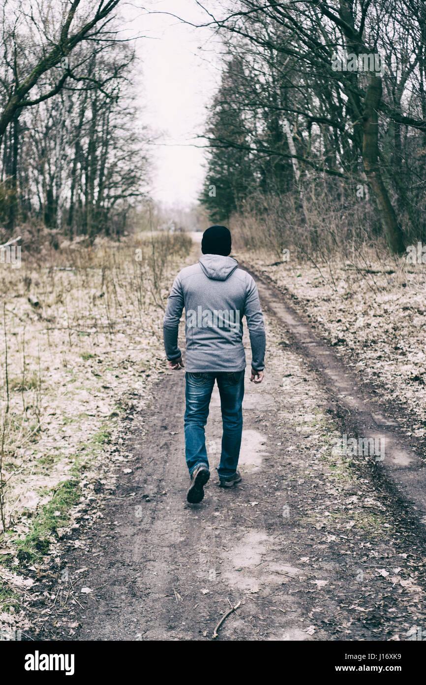 Vue arrière d'un homme marchant sur une route de campagne Photo Stock