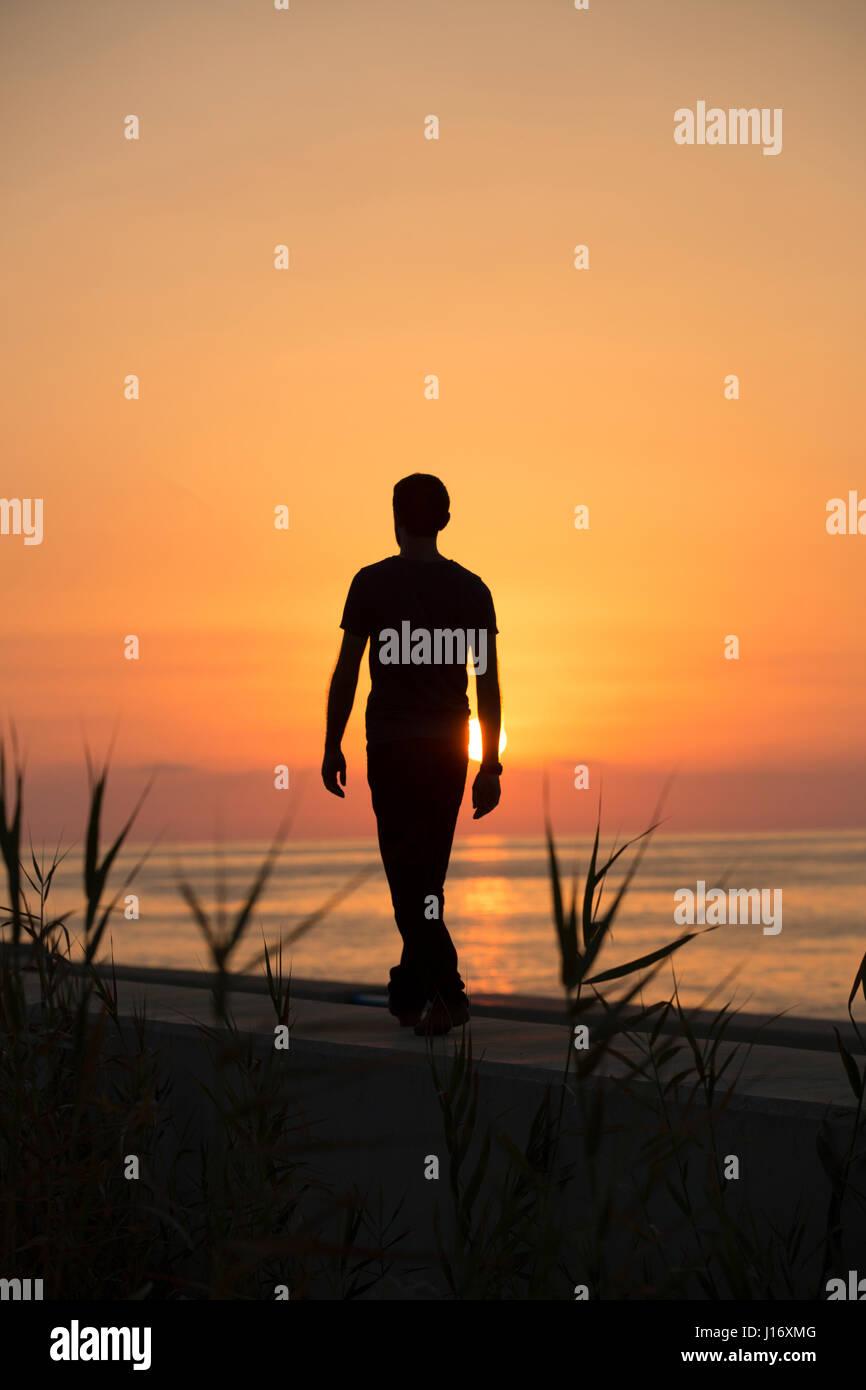 Longueur totale silhouette d'une figure masculine marche sur la plage au coucher du soleil Photo Stock