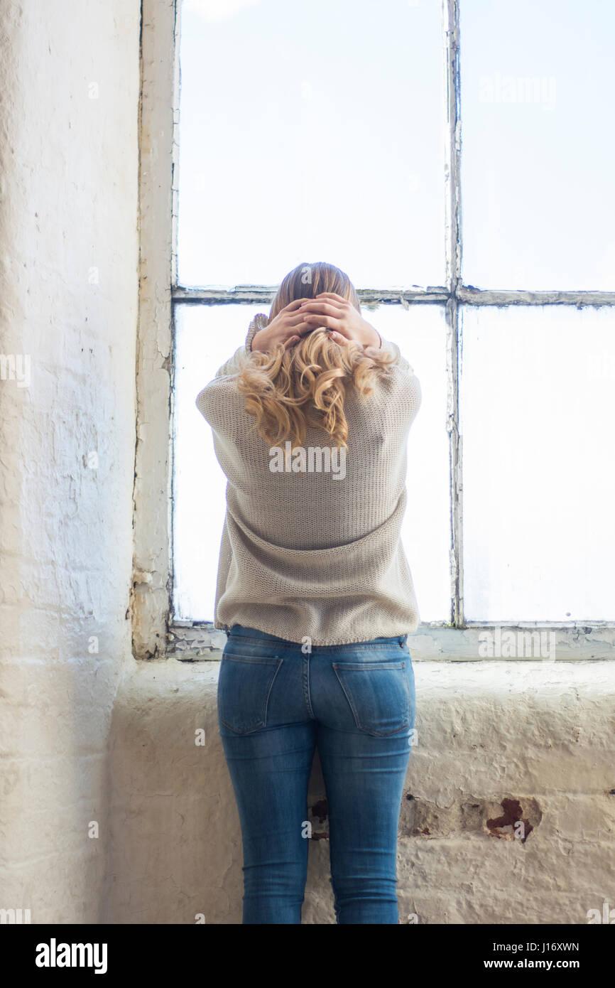 Vue arrière d'une blonde woman standing by a souligné la fenêtre head in hands Photo Stock