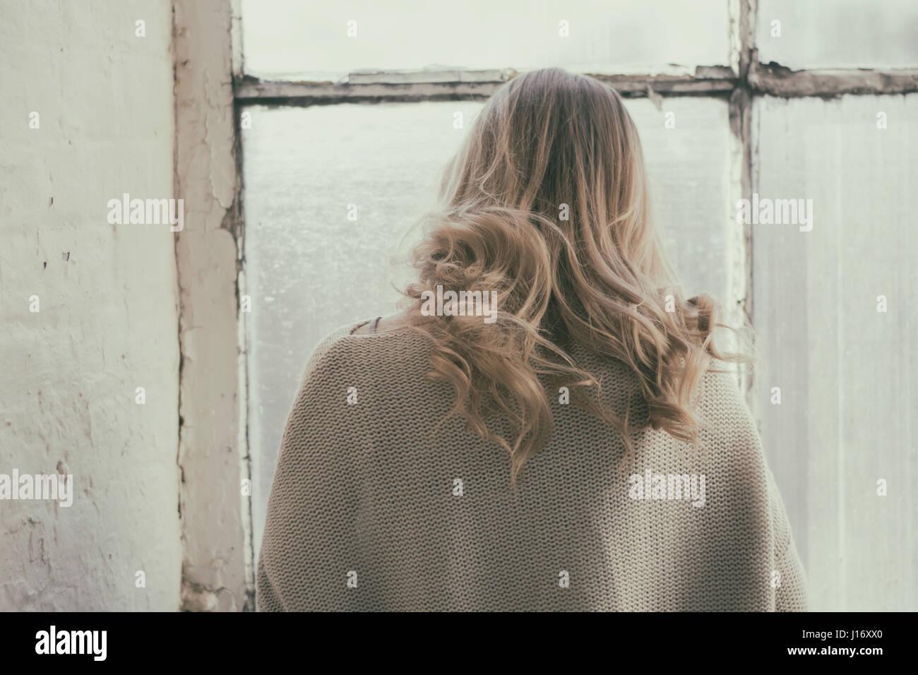 Vue arrière d'une femme blonde debout près de la fenêtre Photo Stock