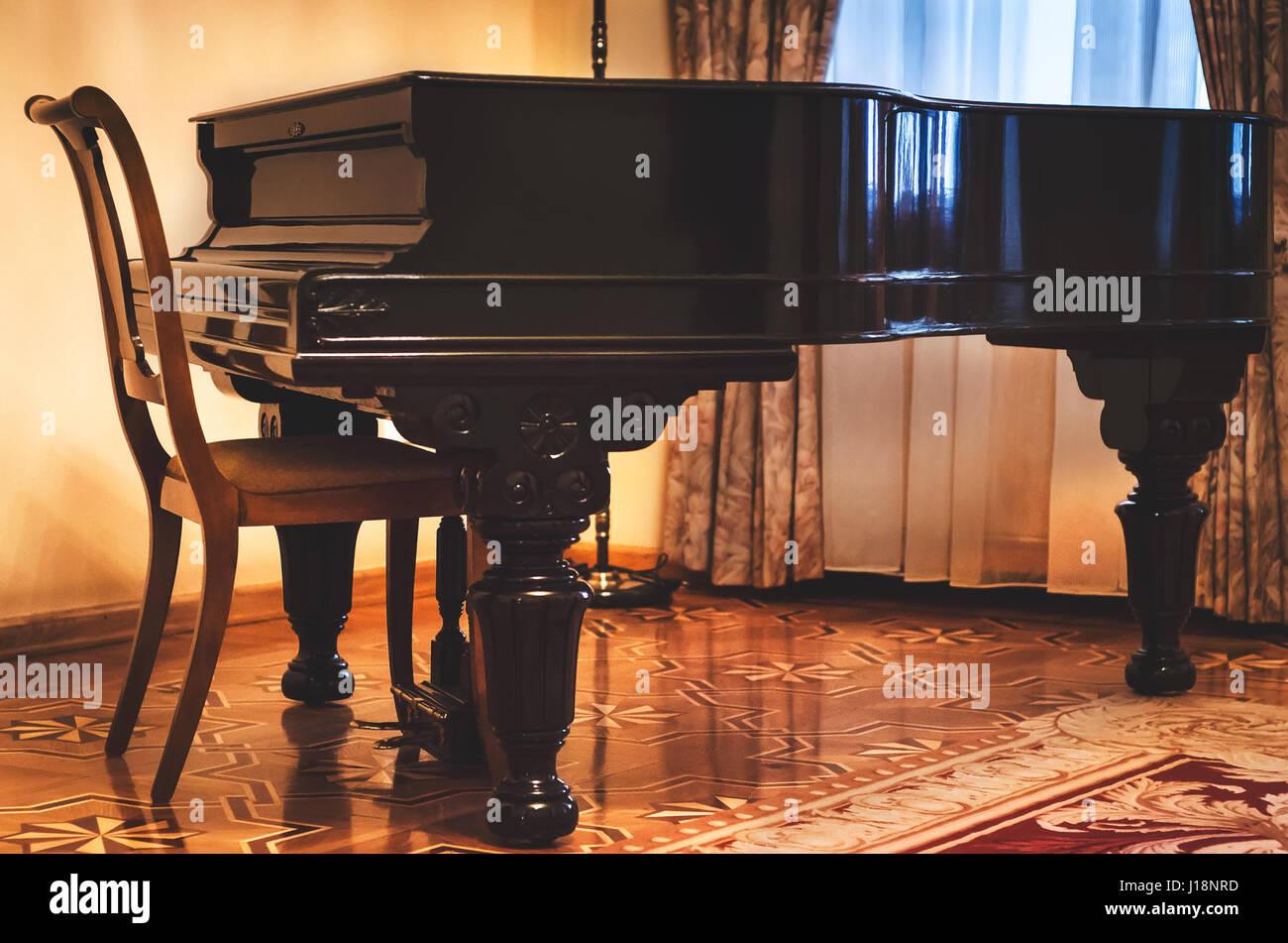 Un piano fermé en bois classique et rétro président en bas ...