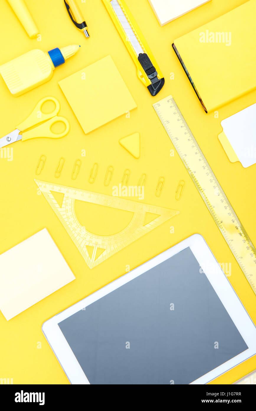 Vue de dessus de tablette numérique avec écran blanc et de fournitures de bureau sur table jaune Photo Stock