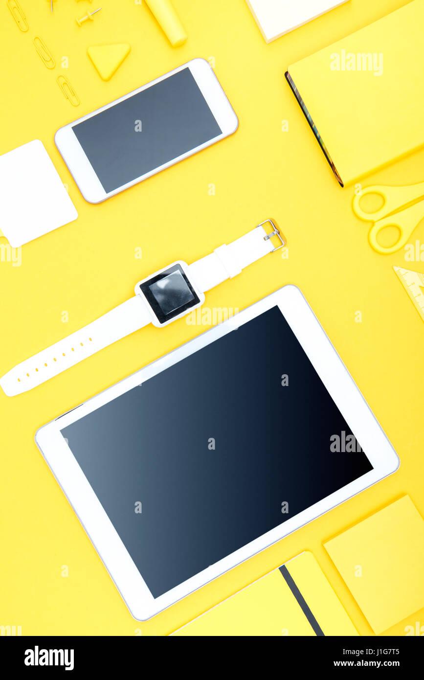 Vue de dessus du smartphone, tablette numérique, smartwatch et des fournitures de bureau sur Photo Stock