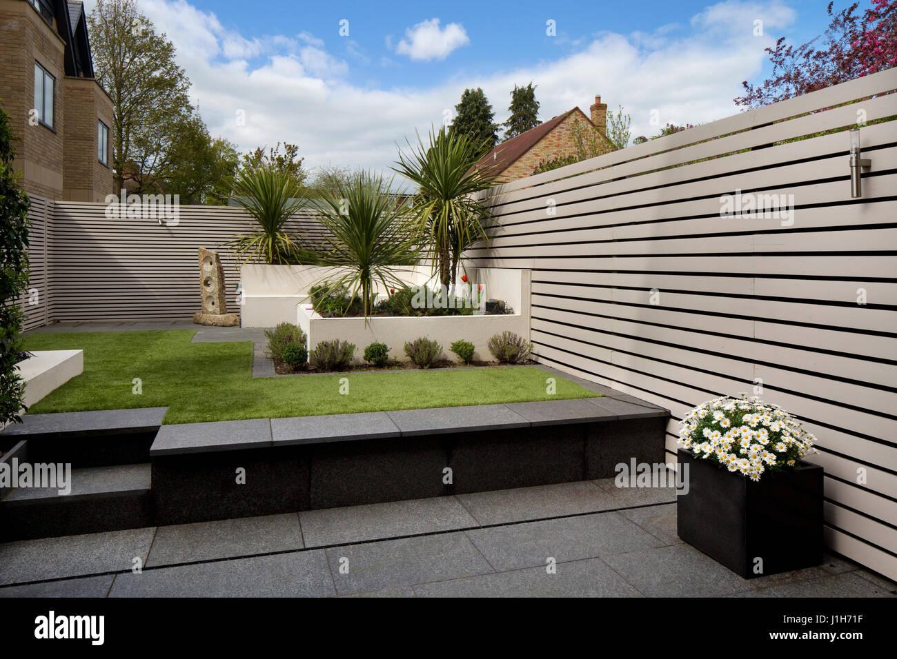 Jardin anglais contemporain moderne avec sol en bois peint clôture ...