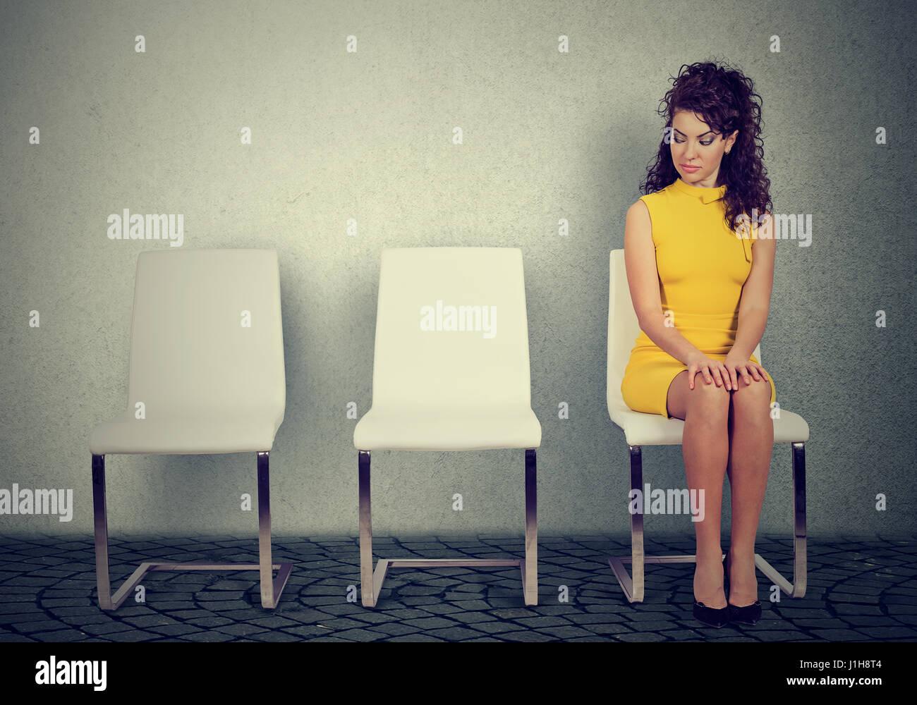 Jeune femme assise sur une chaise en attente d'entrevue d'emploi Photo Stock