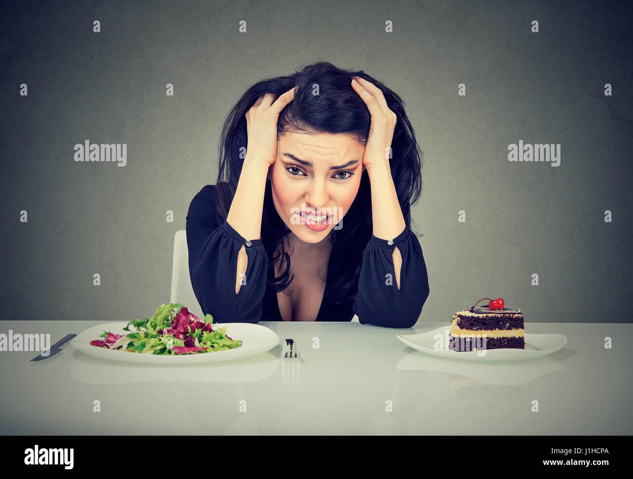 Femme fatigué de décider si les restrictions de régime de manger des aliments sains ou gâteau Photo Stock