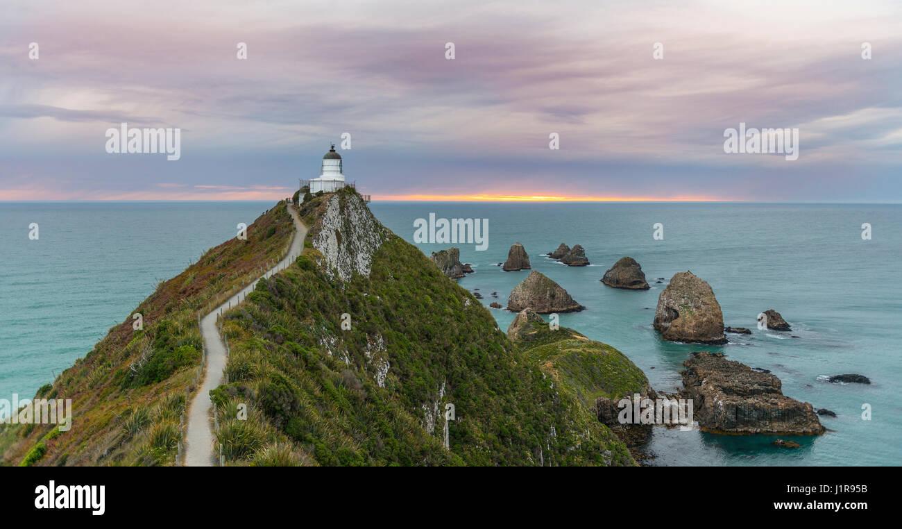 Le lever du soleil, au phare, le Nugget Point, Catlins, Région de l'Otago Southland, Nouvelle-Zélande Photo Stock