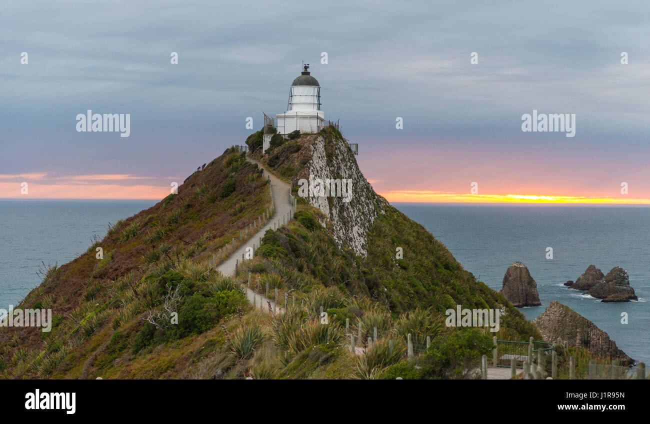 Le lever du soleil, au phare, le Nugget Point, Catlins, Région de l'Otago Southland, Nouvelle-Zélande Photo Stock