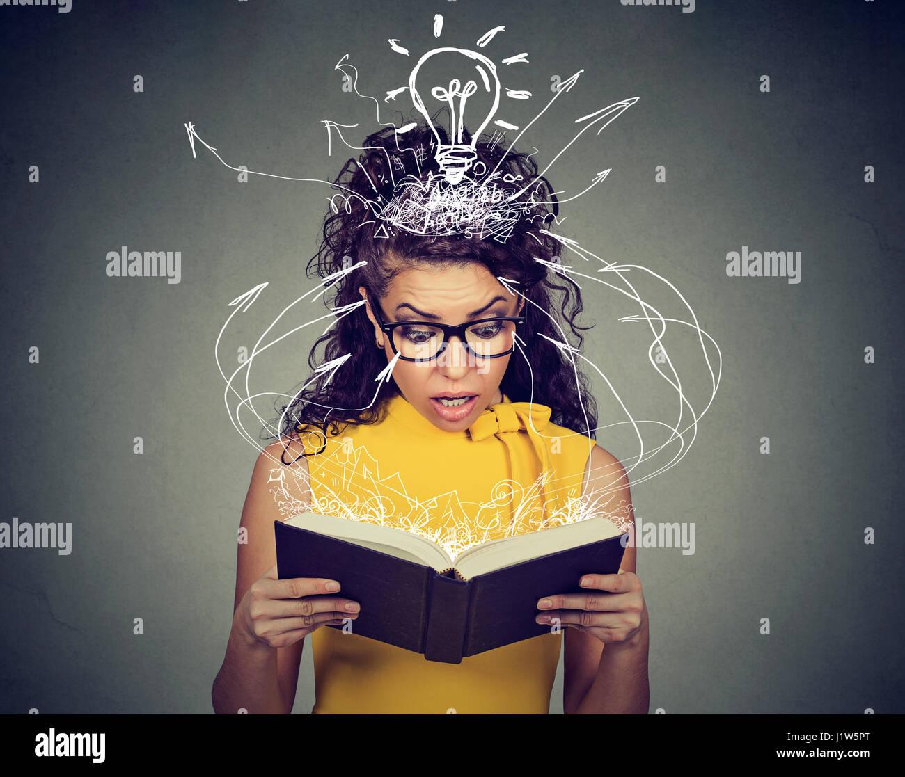 Surpris femme lisant un livre avec des pages brillantes captivé par l'intrigue twist Photo Stock